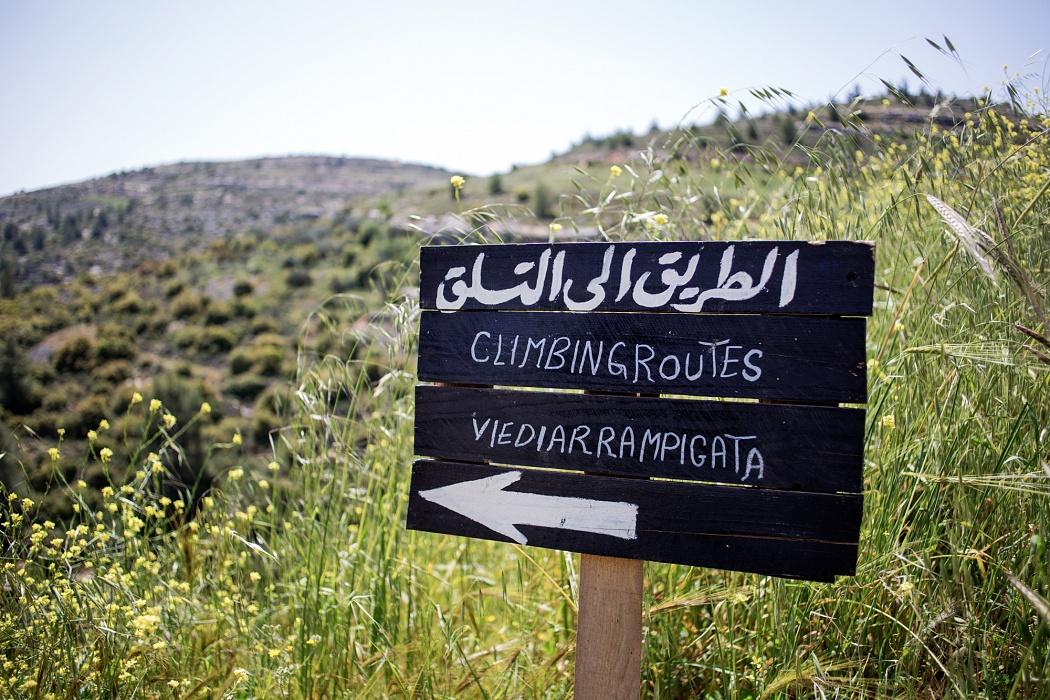 Falesie di Battir, Palestina, 2019 - Il cartello, lungo la strada sterrata nei pressi del villaggio di Battir, indica in arabo, inglese e italiano il sentiero da percorrere per raggiungere le vie di arrampicata allestite sulle falesie.