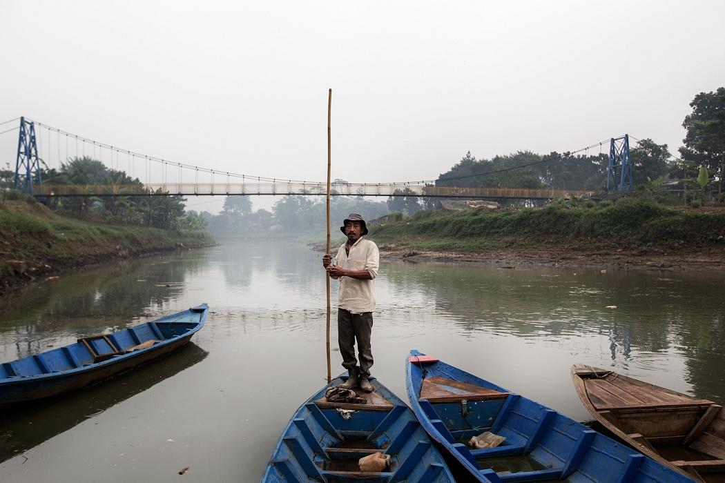 """Sindang Sari village, Baleendah Sub-District, Bandung Regency, West Jawa, Indonesia, 2019 - Il signor Agus, 49 anni, è uno """"scavenger"""", cioè un raccoglitore di materiale riciclabile. Ogni giorno naviga con la sua barca lungo il fiume Citarum e il suo lavoro consiste nel trovare e recuperare i rifiuti da rivendere. Il suo stipendio mensile è di circa 1500000 rupie indonesiane, poco più di 100 euro."""