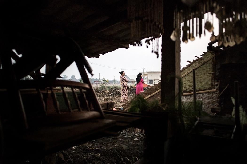 """Babakan Leuwi Bandung village, Dayeuh Kolot Sub-District, Bandung Regency, West Jawa, Indonesia, 2019 - I sedimenti raggiungono la sommità delle case e i primi due piani dell'edificio sono ormai sepolti sotto tonnellate di fango e rifiuti. Il sentiero battuto sulle """"nuove terre"""" permette quindi alle persone di passeggiare accanto ai tetti delle abitazioni."""