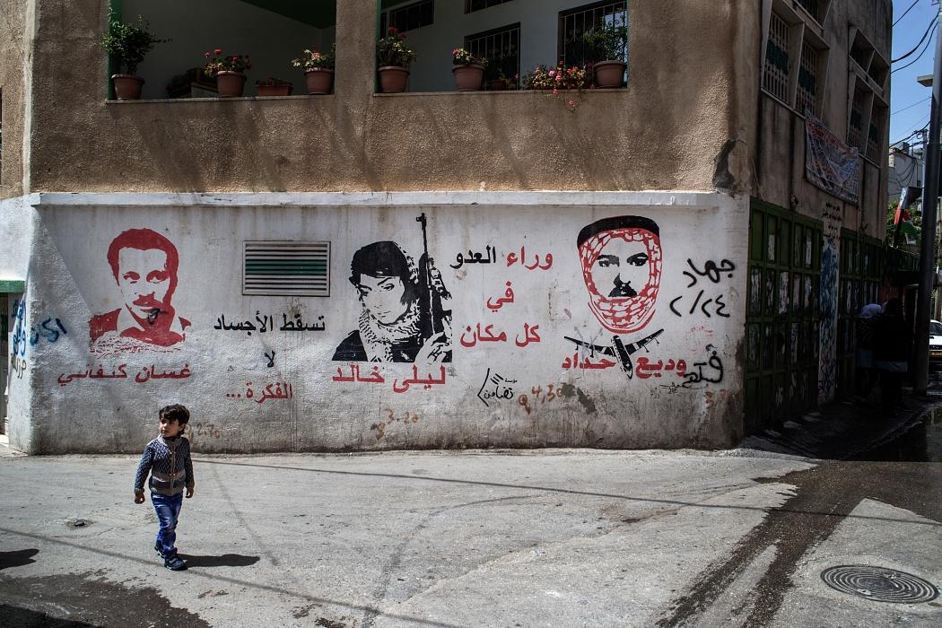 Betlemme, Cisgiordania, Campo profughi di Dheisheh, 2019 - I muri del campo profughi di Dheisheh raccontano le tappe dell'intifada e rendono omaggio a militanti, combattenti, martiri e intellettuali vicino al movimento di liberazione della Palestina. Fra i volti ritratti su uno dei muri del campo Ghassan Kanafani, a sinistra, fu scrittore, giornalista e attivista legato al FPLP e venne ucciso con un attacco incendiario che, si dice, fu ordinato dal Mossad. Al centro  invece Leila Khaled, politica e terrorista palestinese protagonista di due dirottamenti aerei e anch'essa membro del FPLP, Il Fronte Nazionale per la Liberazione della Palestina.