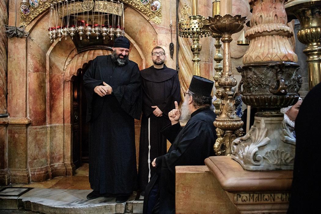 Chiesa del Santo Sepolcro, Gerusalemme, aprile 2019 - Due monaci della Chiesa Greco Ortodossa e un frate francescano conversano in prossimità del Santo Sepolcro, in attesa dell'ingresso del Patriarca della Chiesa Greco Ortodossa di Gerusalemme Teofilo III.