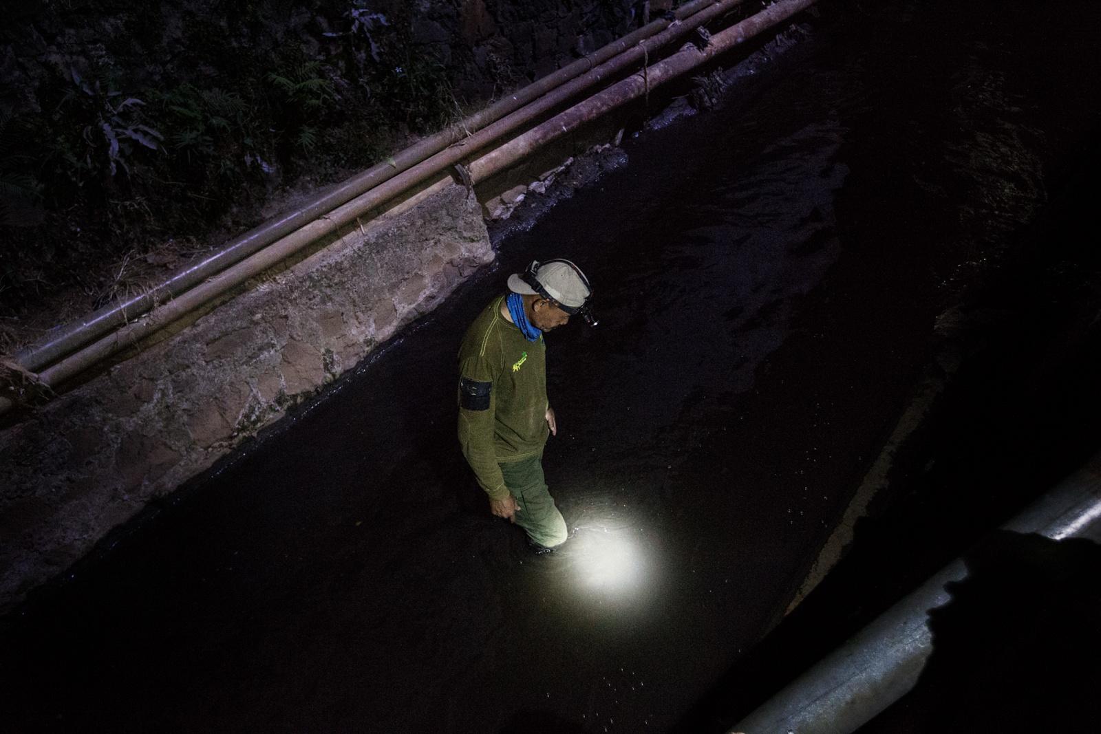 """Majalaya Area, Bandung Regency, West Jawa, Indonesia, 2019 - Mr. Alit, attivista ambientalista di Badega Lingkungan, controlla un canale nell'area industriale della città di Majalaya alla ricerca di scarichi abusivi durante il progetto """"Citarum water patrol"""". L'acqua torbida in cui cammina è altamente inquinata e spesso causa prurito, dermatiti da contatto e rash cutaneo."""