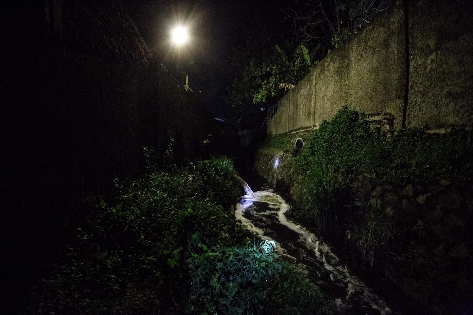 Majalaya Area, Bandung Regency, West Jawa, Indonesia, 2019 - Lungo un canale, in un'area nascosta e inaccessibile della zona industriale di Majalaya, una fabbrica tessile scarica direttamente dentro al fiume gli scarti del proprio processo produttivo. .