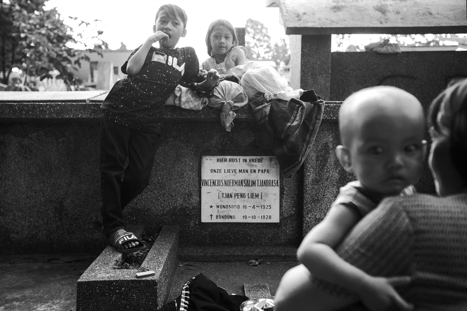 Bandung City, Bandung Regency, West Java, Indonesia, 2019 - Netti, 35 anni, siede insieme al più piccolo dei suoi 4 figli sul basamento di una delle tombe adiacenti al suo rifugio.